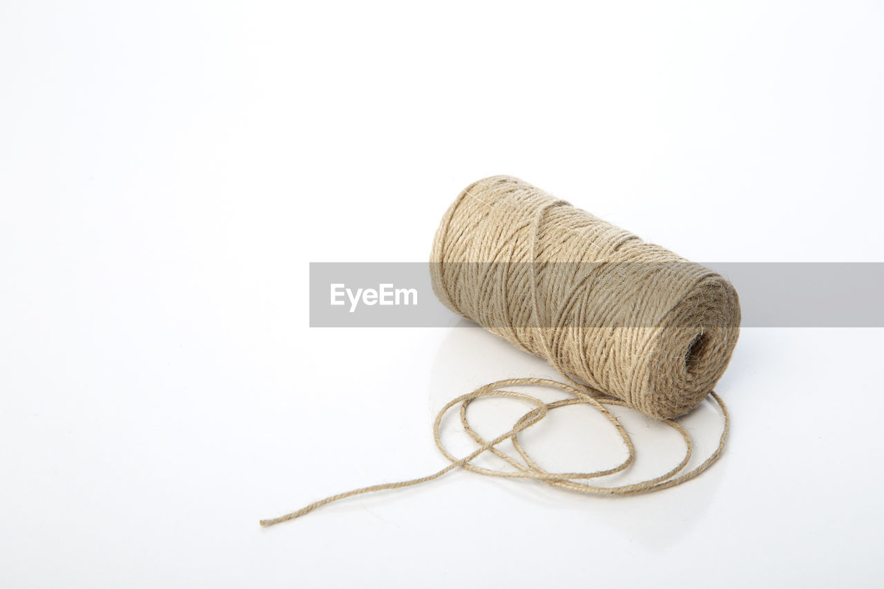 Close-Up Of Wool Spool Over White Background