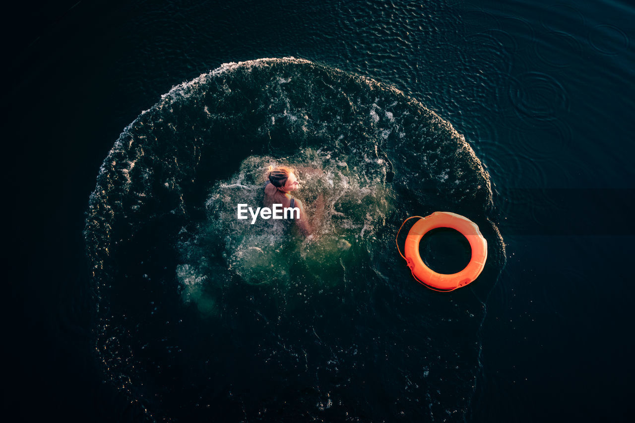 Woman With Inflatable Ring Swimming In Sea