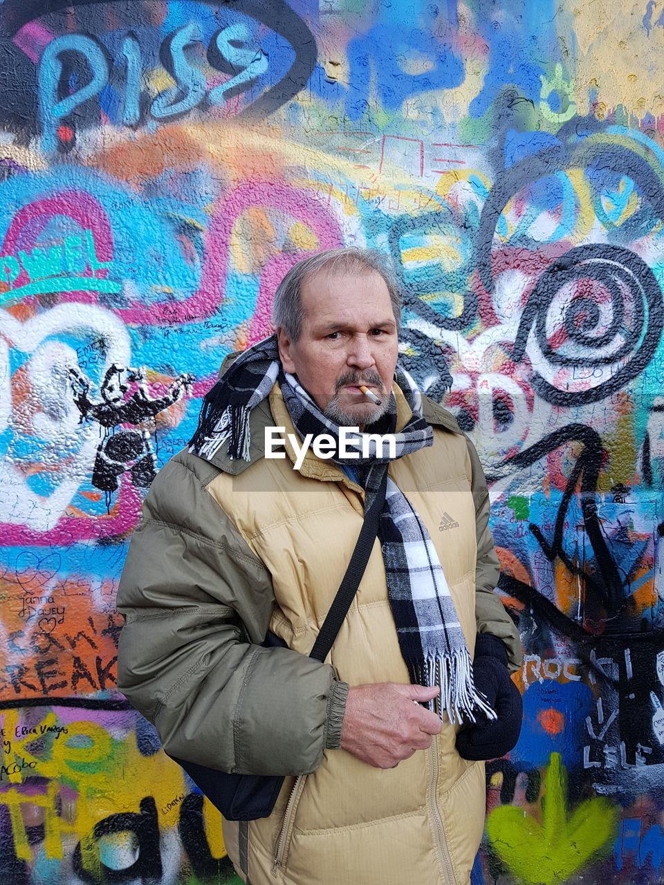 Portrait of man smoking cigarette against graffiti wall