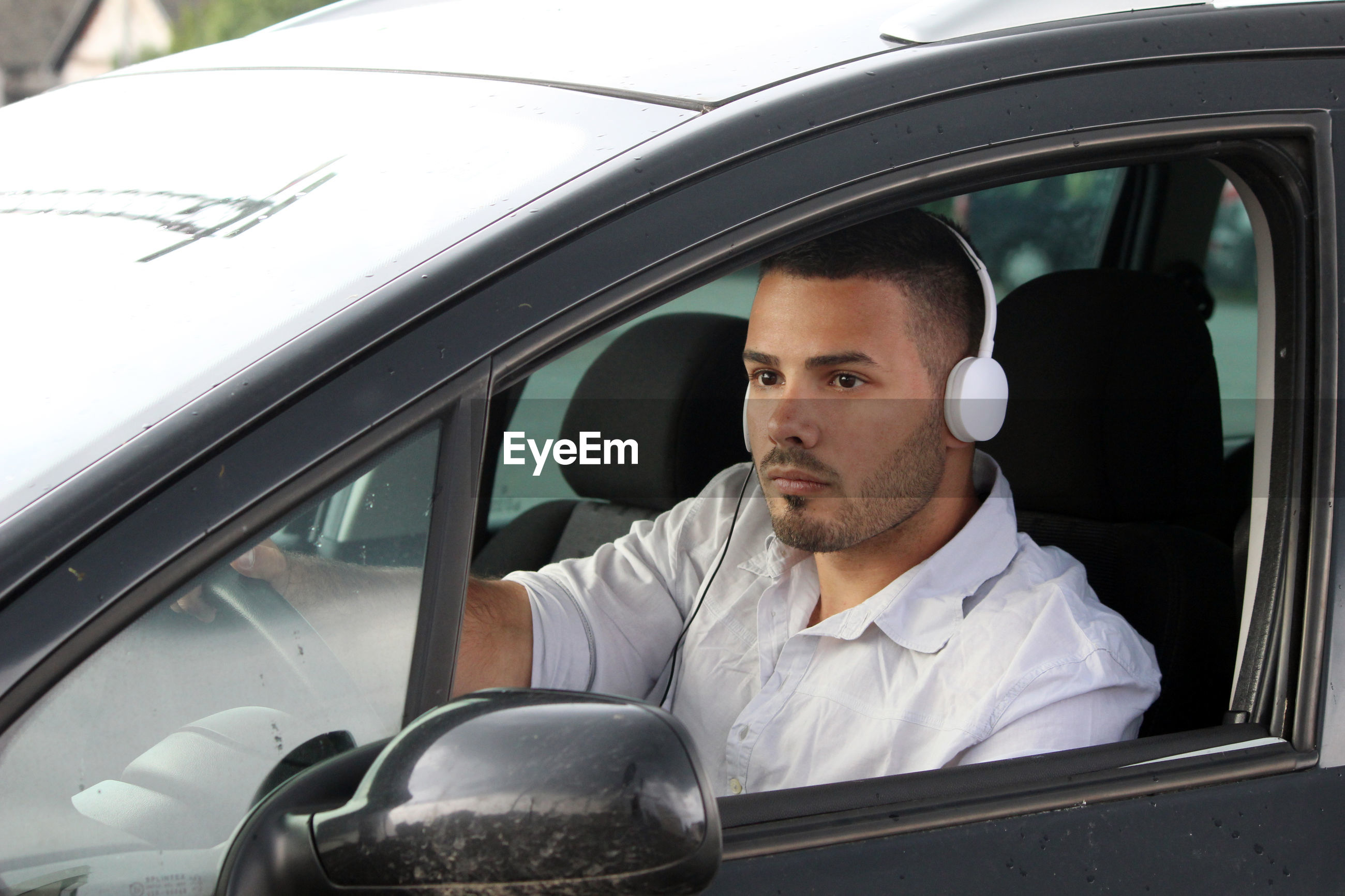Man wearing headphones driving car seen through window