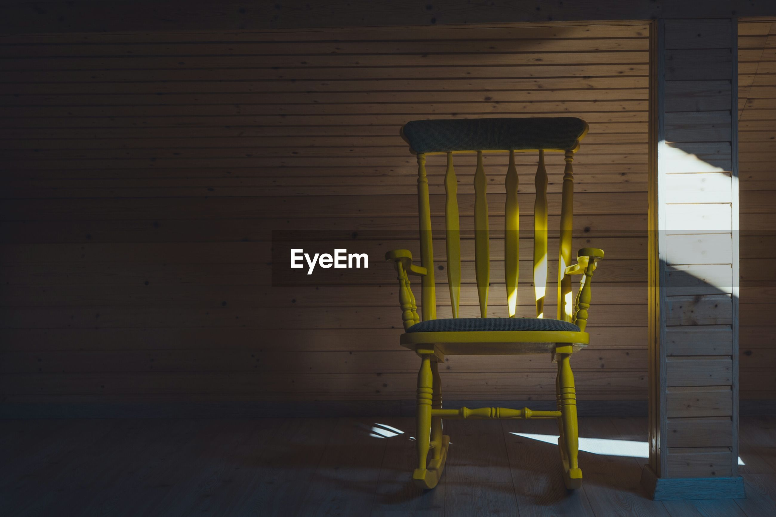 Sunlight falling on empty yellow rocking chair by wooden wall