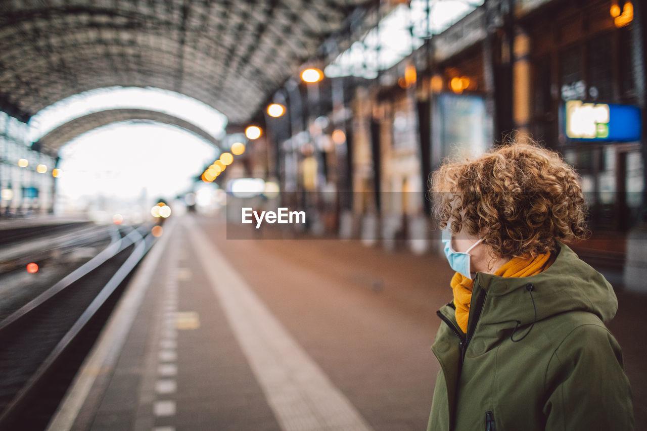Portrait of woman on railroad station wearing a mask
