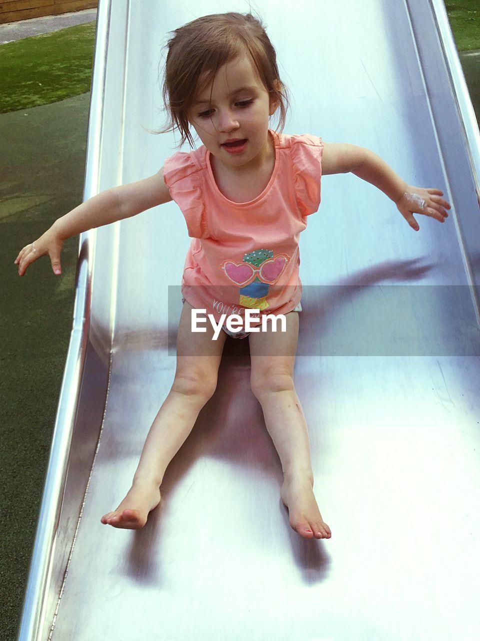 Full length of girl enjoying on slide at park