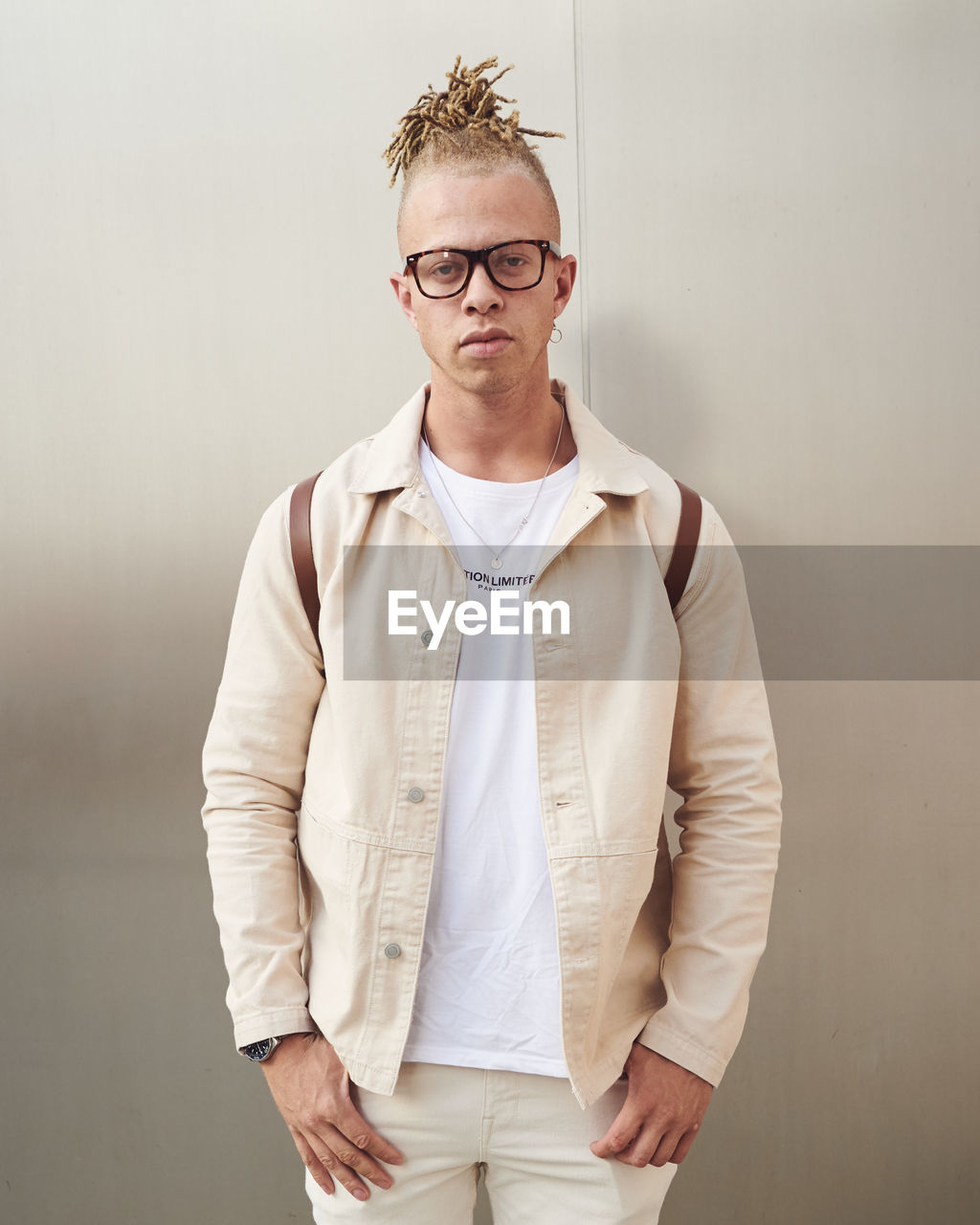 one person, standing, front view, glasses, eyeglasses, young men, young adult, three quarter length, real people, indoors, button down shirt, wall - building feature, looking at camera, clothing, waist up, portrait, men, lifestyles, menswear
