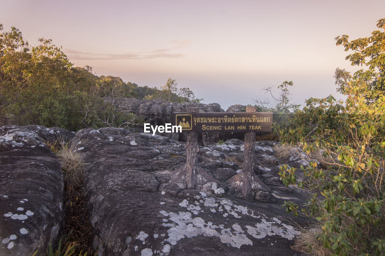 text, western script, sign, communication, tree, nature, plant, sky, information, no people, information sign, sunset, environment, day, outdoors, non-urban scene, rock, guidance, landscape, tranquility