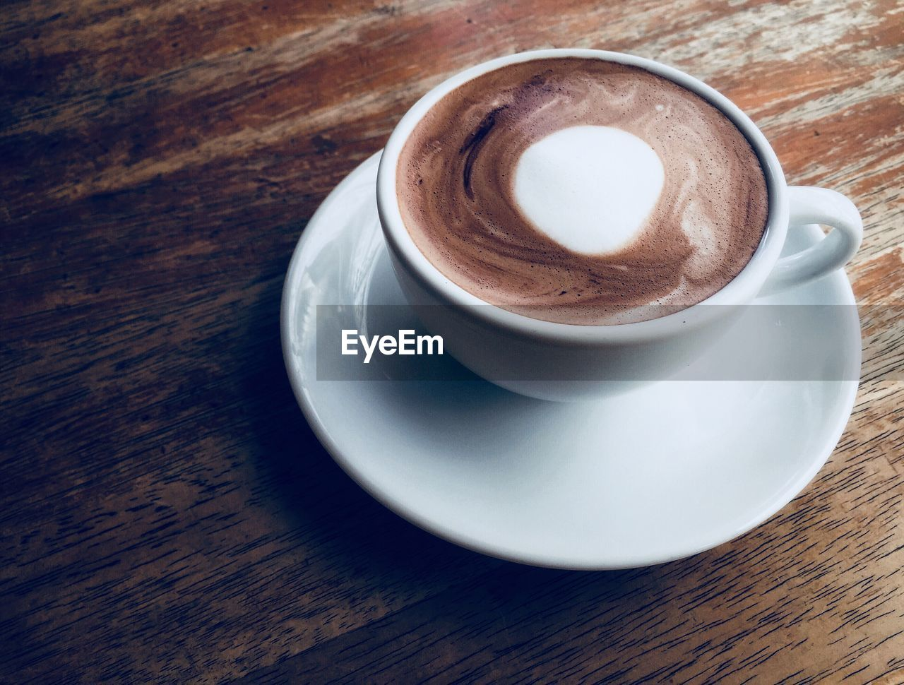 coffee cup, coffee, coffee - drink, drink, still life, food and drink, refreshment, mug, table, frothy drink, cup, crockery, saucer, freshness, close-up, indoors, high angle view, wood - material, cappuccino, hot drink, no people, positive emotion, latte, non-alcoholic beverage, froth, temptation
