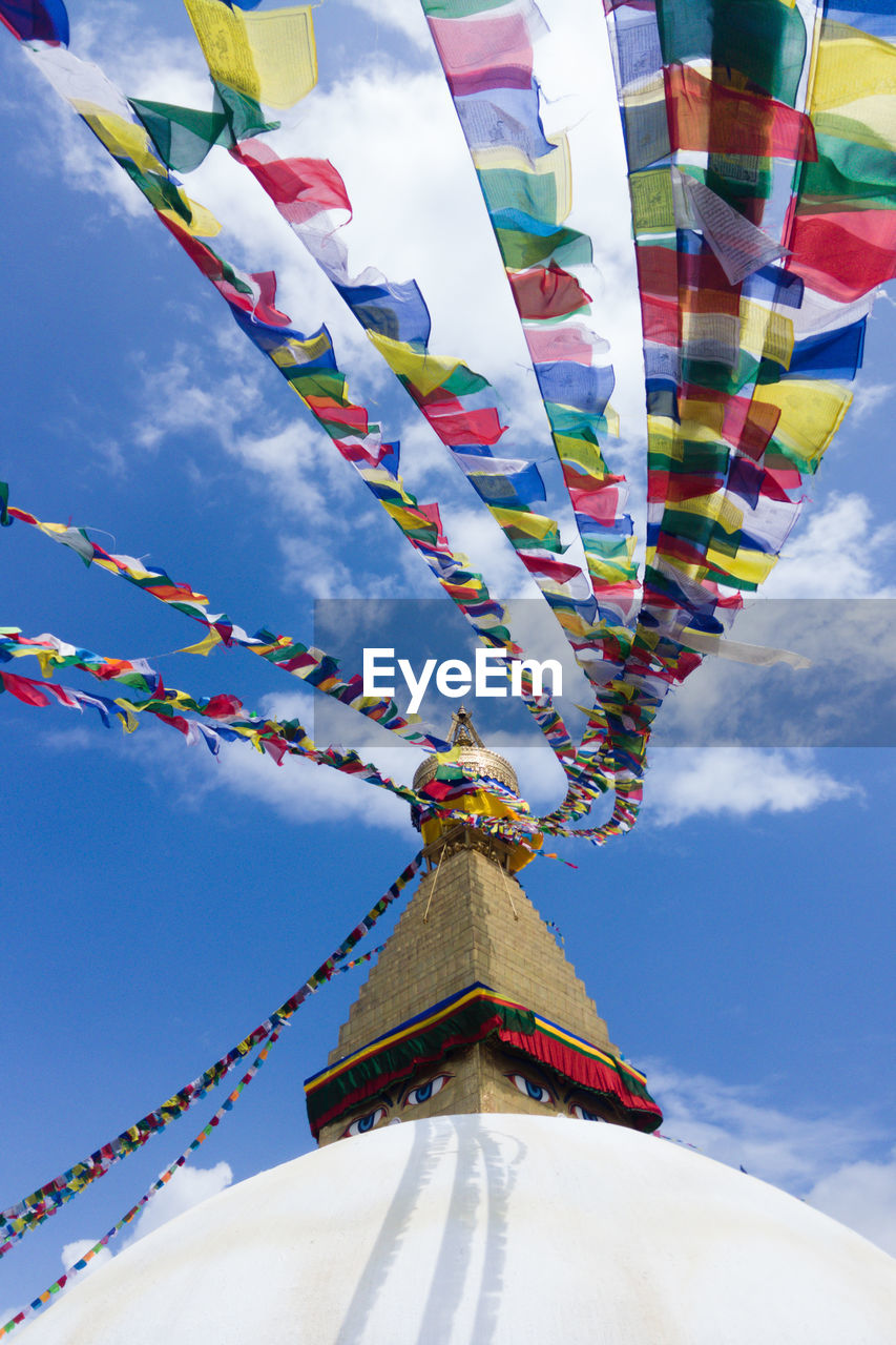 cloud - sky, sky, multi colored, low angle view, belief, no people, decoration, celebration, bunting, day, flag, religion, spirituality, nature, architecture, built structure, hanging, outdoors