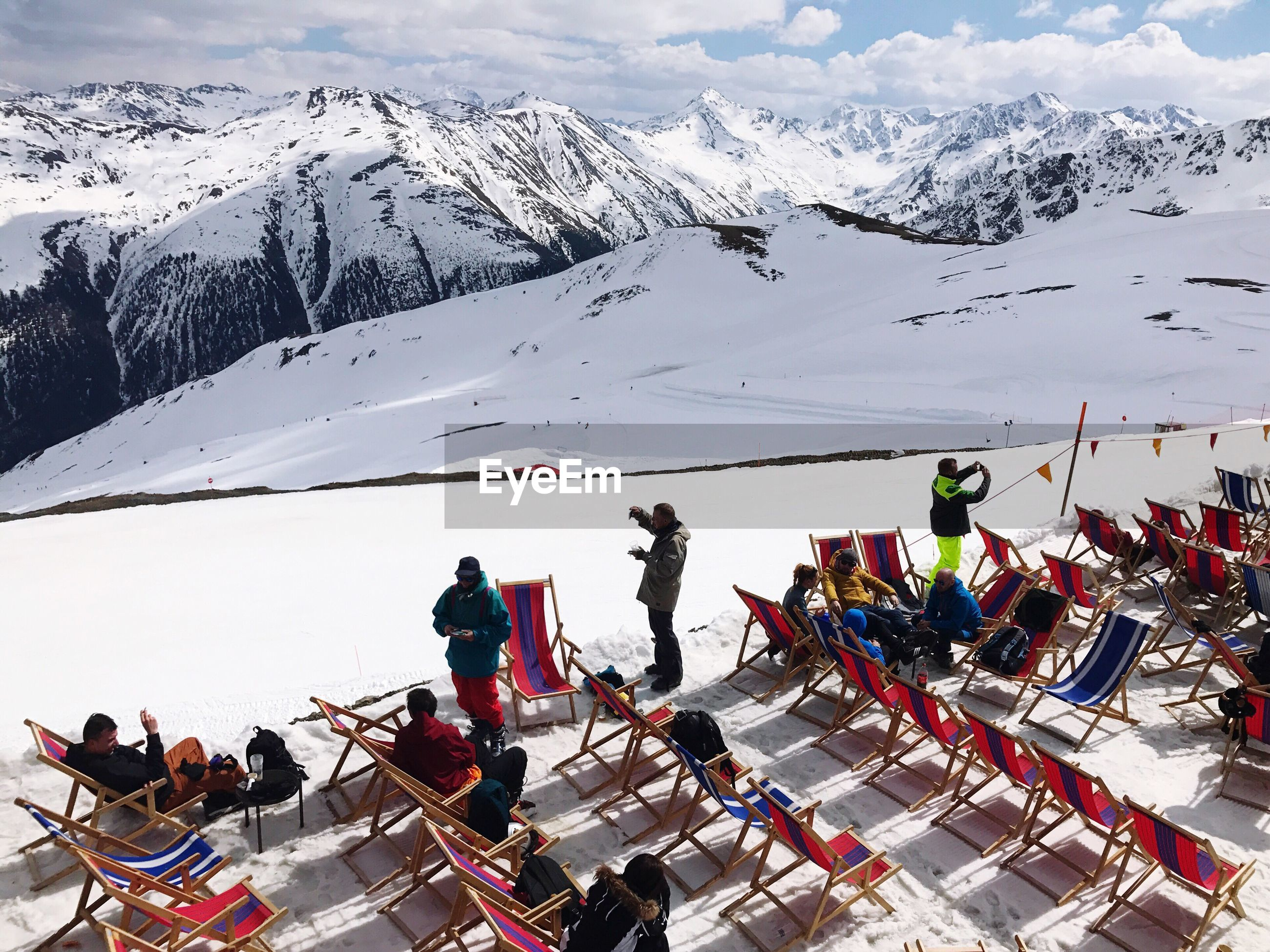 People on chairs at snow covered mountain