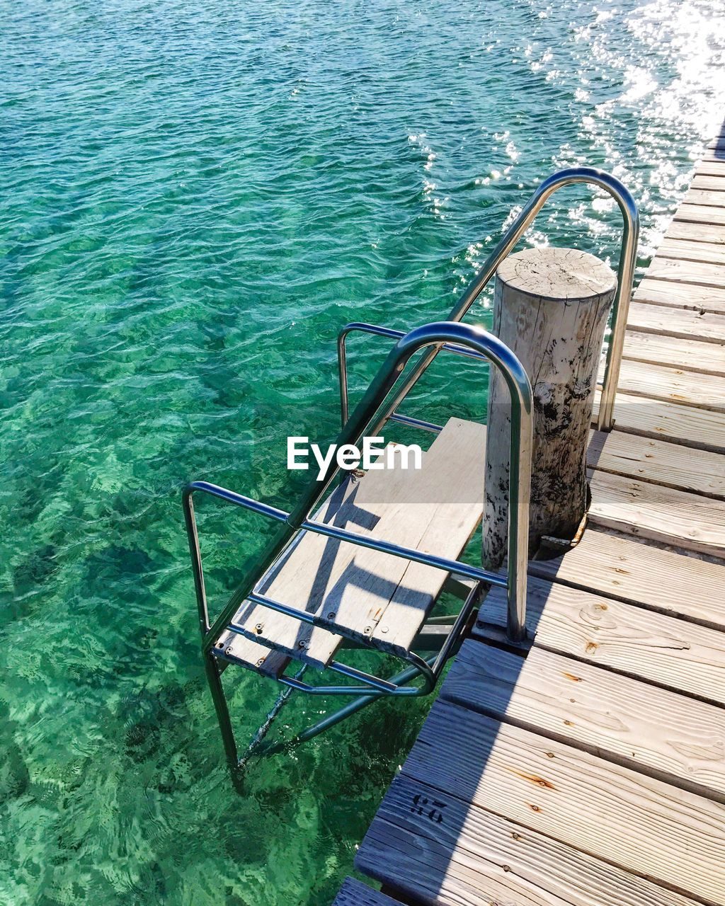 water, nature, high angle view, no people, pool, swimming pool, seat, absence, day, wood - material, railing, tranquility, sunlight, ladder, chair, sea, staircase, outdoors, pier, turquoise colored