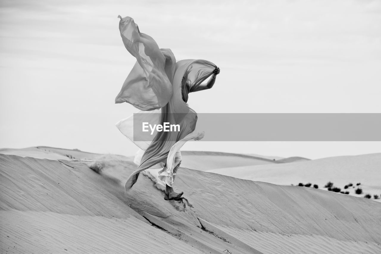Woman With Fabric Jumping Over Sand At Beach Against Sky