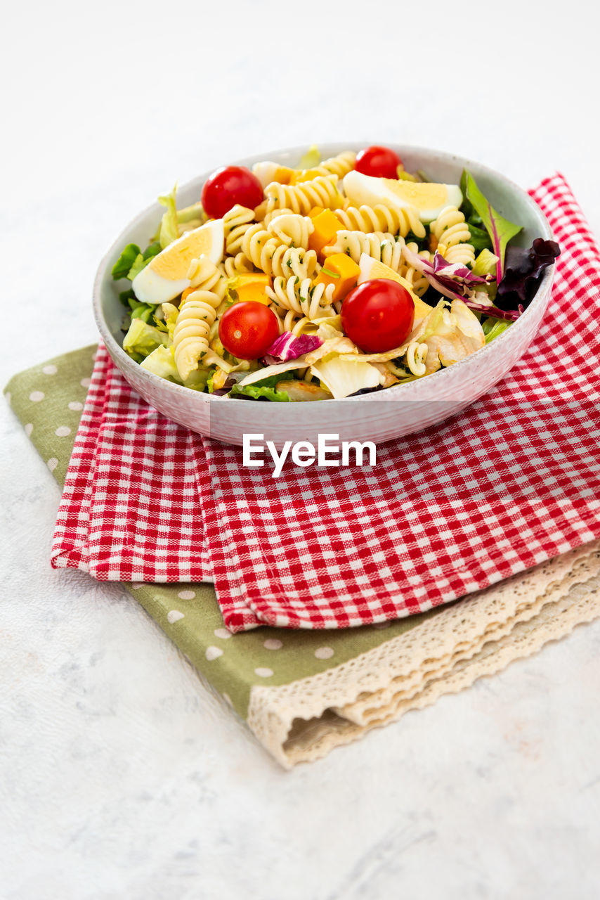 food, food and drink, healthy eating, freshness, vegetable, wellbeing, fruit, pasta, tomato, still life, italian food, red, ready-to-eat, indoors, table, napkin, high angle view, bowl, checked pattern, close-up, no people, vegetarian food, spaghetti