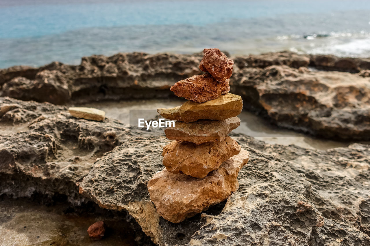 sea, rock, focus on foreground, land, beach, solid, rock - object, water, nature, no people, day, close-up, textured, stack, outdoors, rough, tranquility, brown, balance