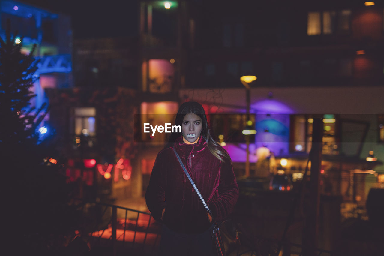 night, illuminated, one person, standing, young adult, lifestyles, looking at camera, leisure activity, real people, front view, portrait, young women, architecture, women, waist up, building exterior, three quarter length, focus on foreground, built structure, city, beautiful woman, outdoors, nightlife, hairstyle, warm clothing