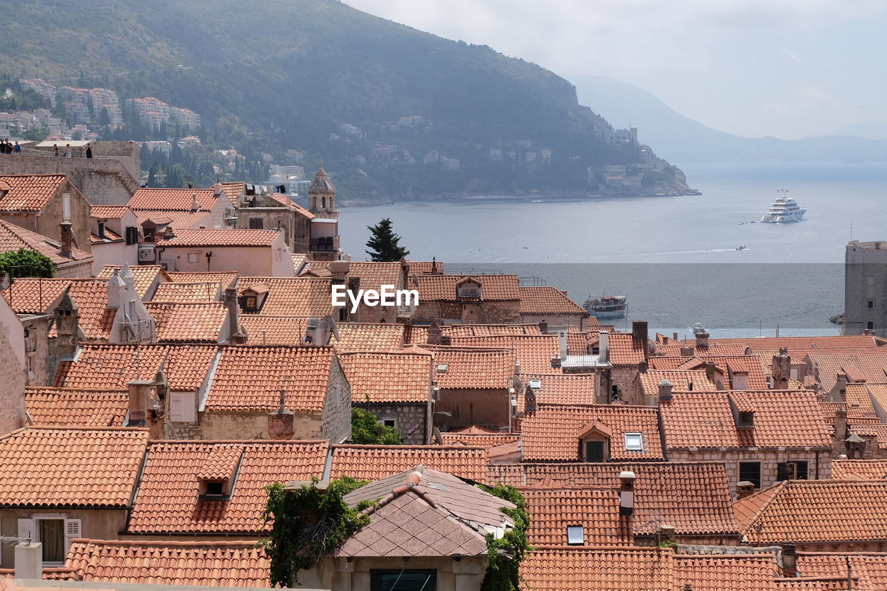 architecture, building exterior, built structure, roof, building, city, high angle view, water, residential district, town, mountain, nature, day, house, sea, no people, outdoors, community, roof tile, townscape