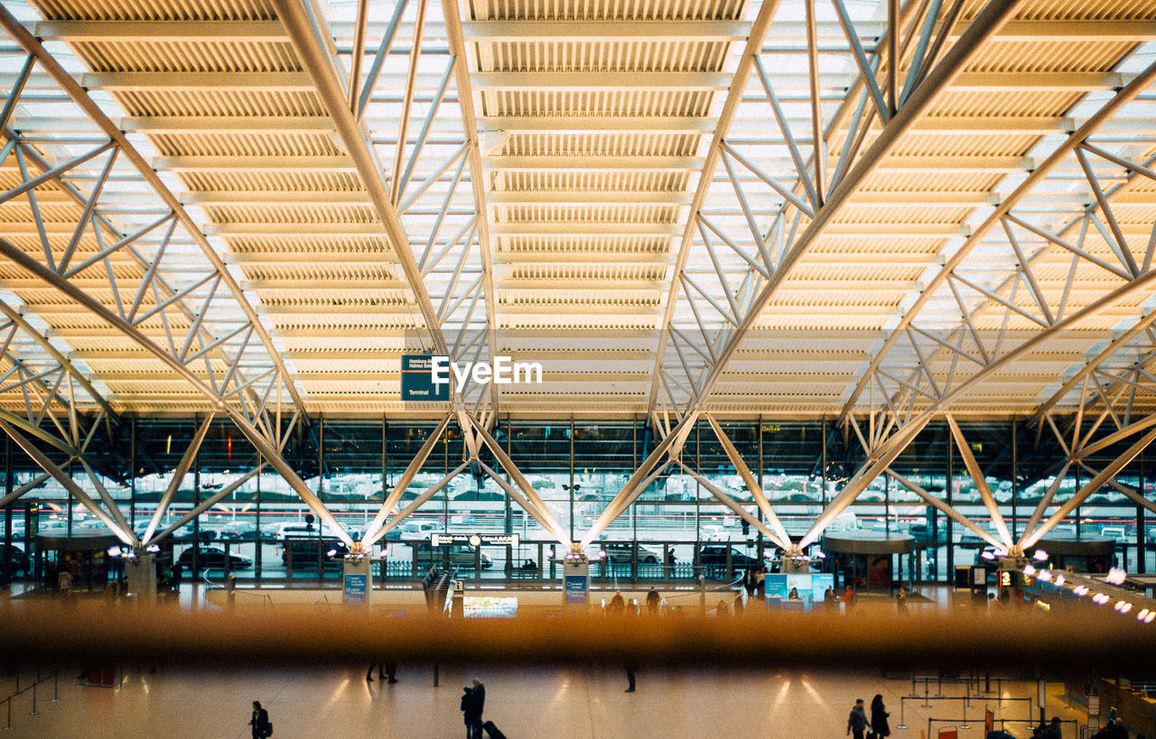 real people, large group of people, ceiling, indoors, men, lifestyles, passenger, architecture, leisure activity, illuminated, built structure, airport, women, day, crowd, neon, people, adult, adults only