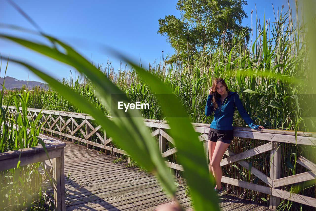 Portrait of young woman standing on footbridge by railing at field during sunny day