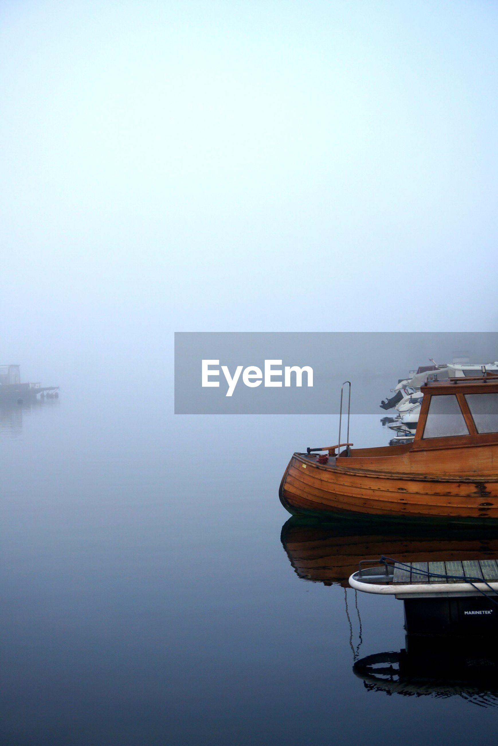 Motorboats moored in fog