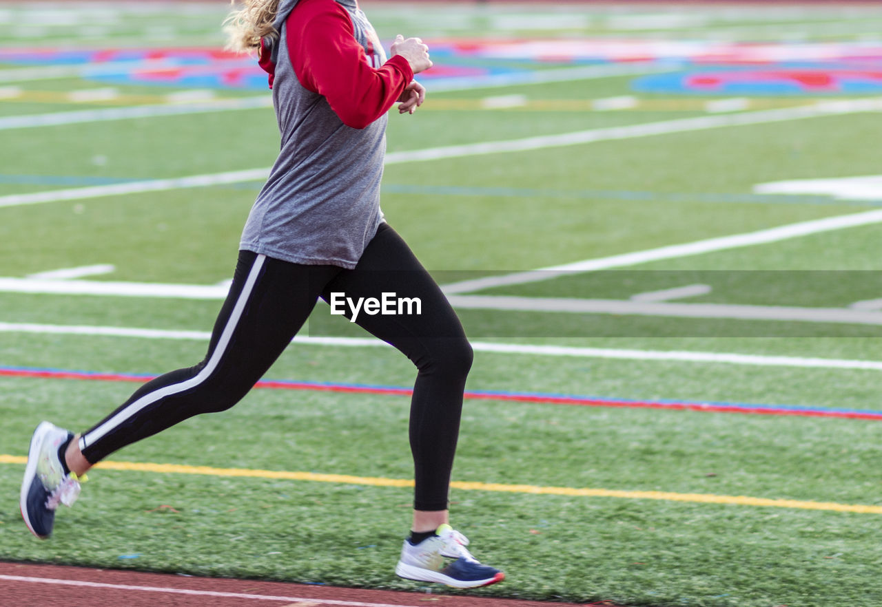 Midsection of woman running on field