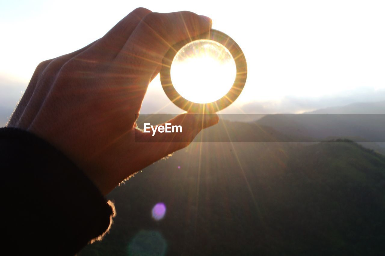 Cropped hand of man holding lens against mountains during sunset