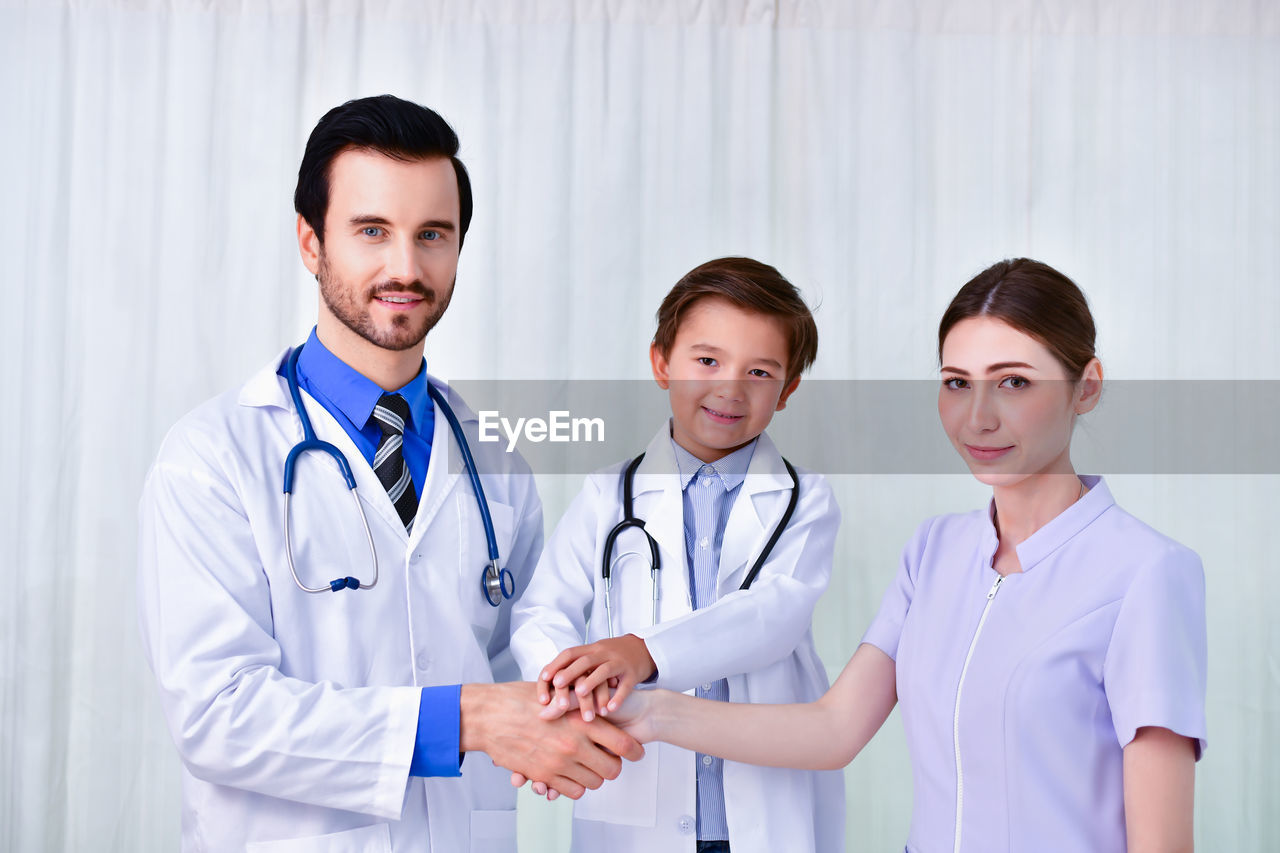 doctor, occupation, healthcare and medicine, medical supplies, medical instrument, medical equipment, clothing, lab coat, stethoscope, hospital, looking at camera, adult, indoors, front view, standing, young men, young adult, men, people, coworker, care, healthcare worker