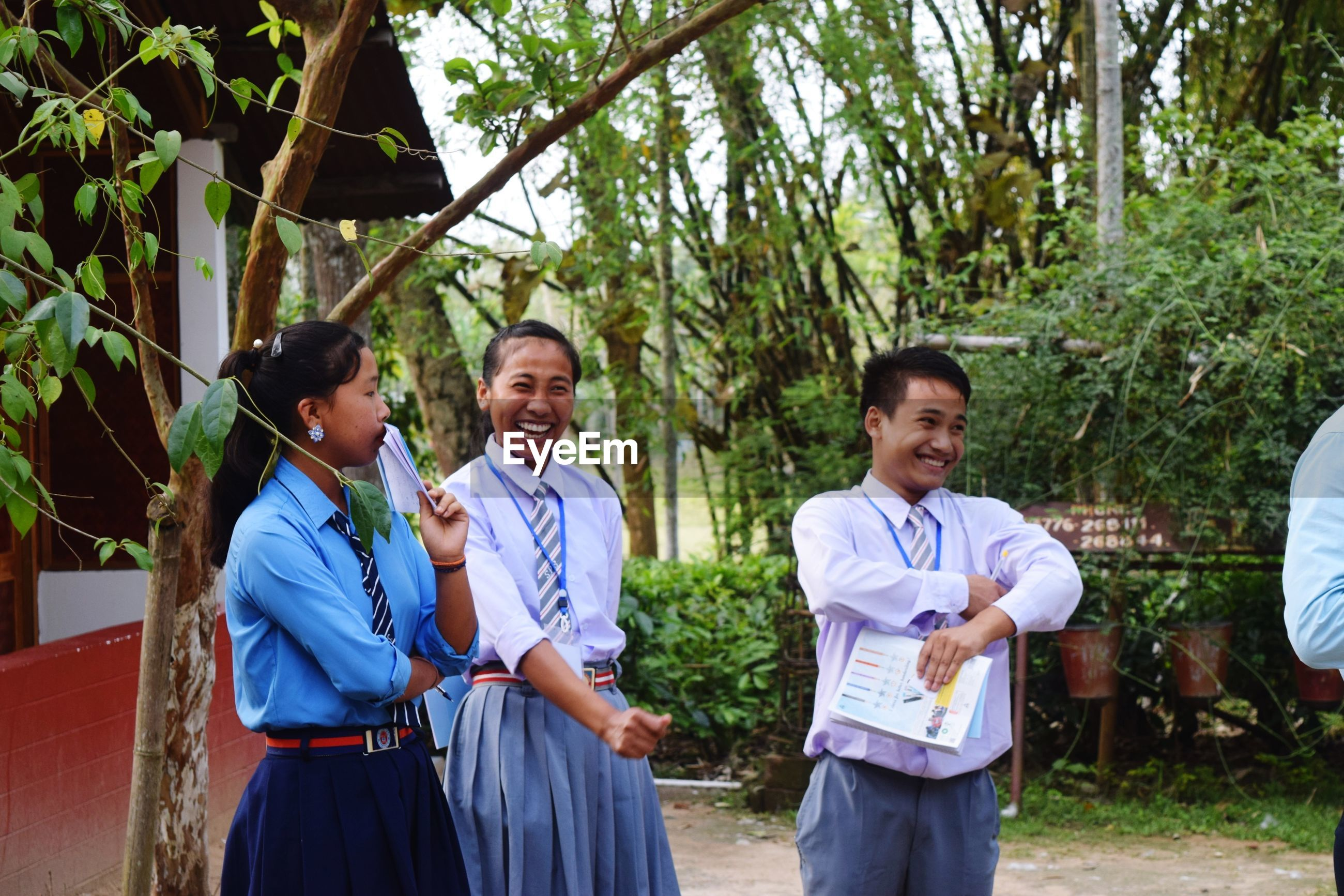 Students smiling while standing against trees