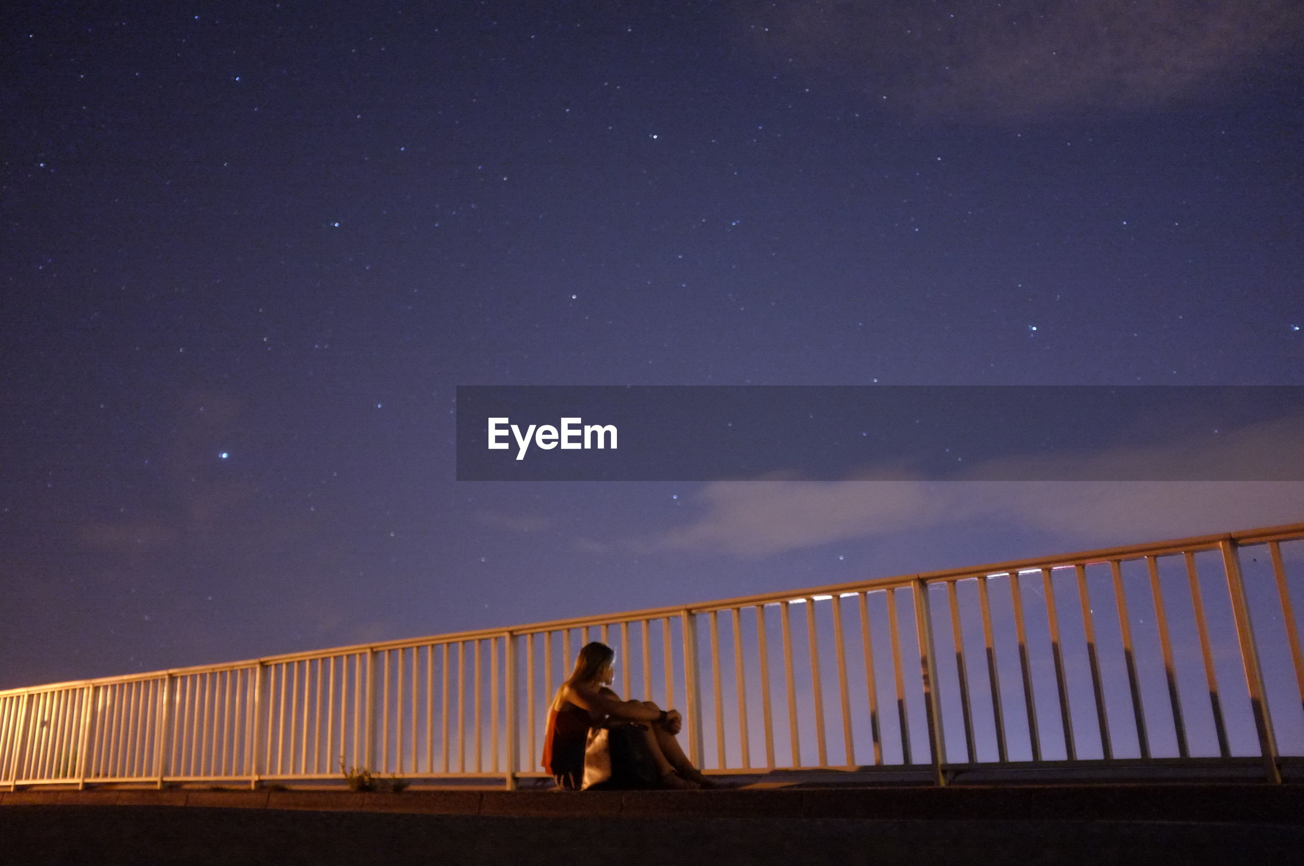 Young woman sitting on bridge at night