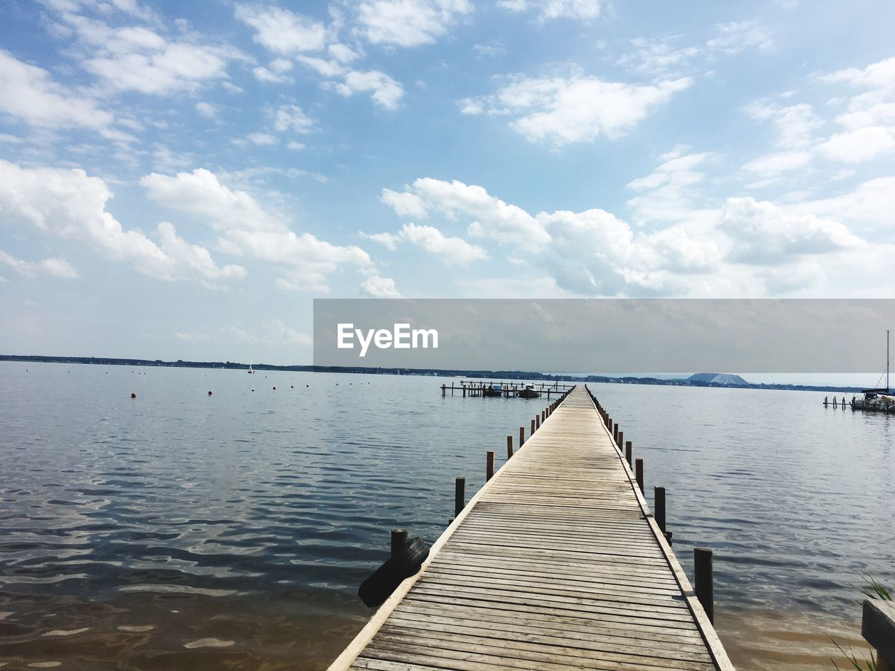 water, sky, cloud - sky, tranquility, tranquil scene, beauty in nature, wood - material, pier, scenics - nature, the way forward, direction, no people, jetty, nature, lake, day, idyllic, built structure, diminishing perspective, wood paneling, outdoors, wood, long