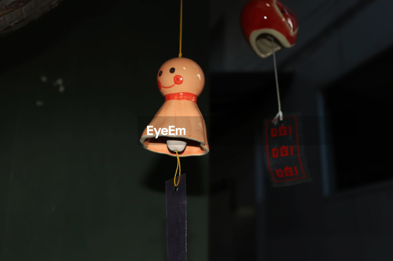 hanging, representation, no people, focus on foreground, human representation, close-up, indoors, toy, lighting equipment, string, creativity, art and craft, red, male likeness, decoration, low angle view, female likeness, night, orange color