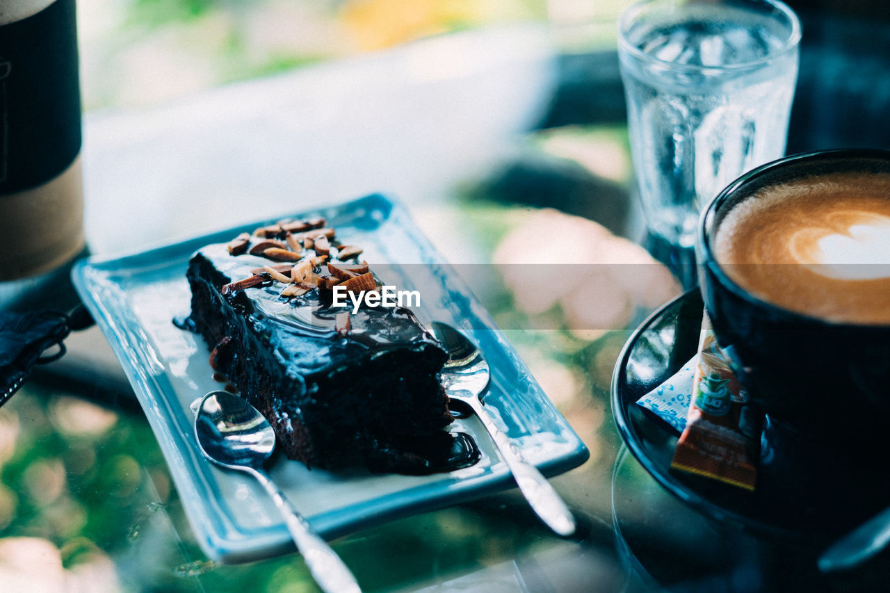 Close-Up Of Cake By Coffee Cup In Plate On Table