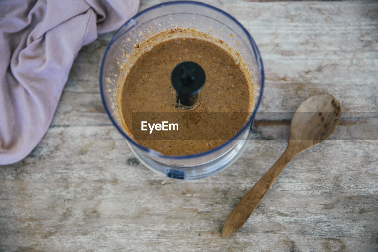kitchen utensil, eating utensil, spoon, food and drink, high angle view, food, indoors, freshness, directly above, table, wood - material, close-up, no people, household equipment, still life, drink, bowl, cup, container, coffee - drink, breakfast, crockery