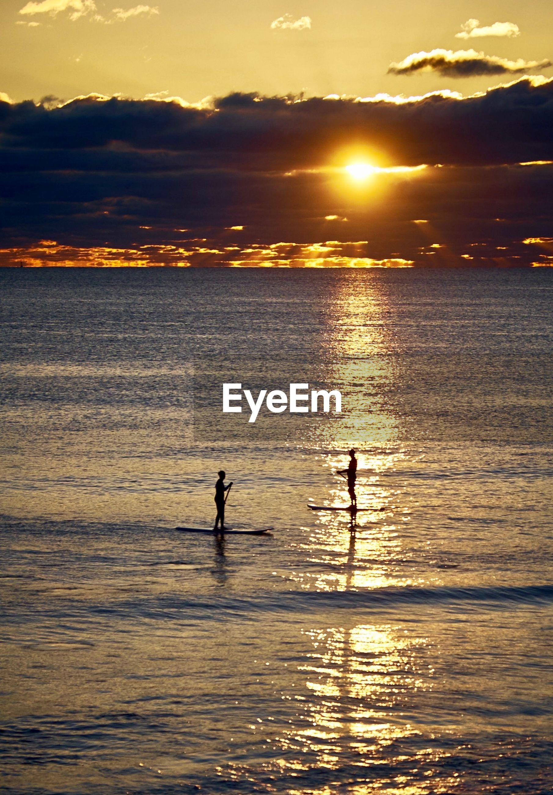 High angle view of silhouette people paddleboarding on sea against cloudy sky during sunset