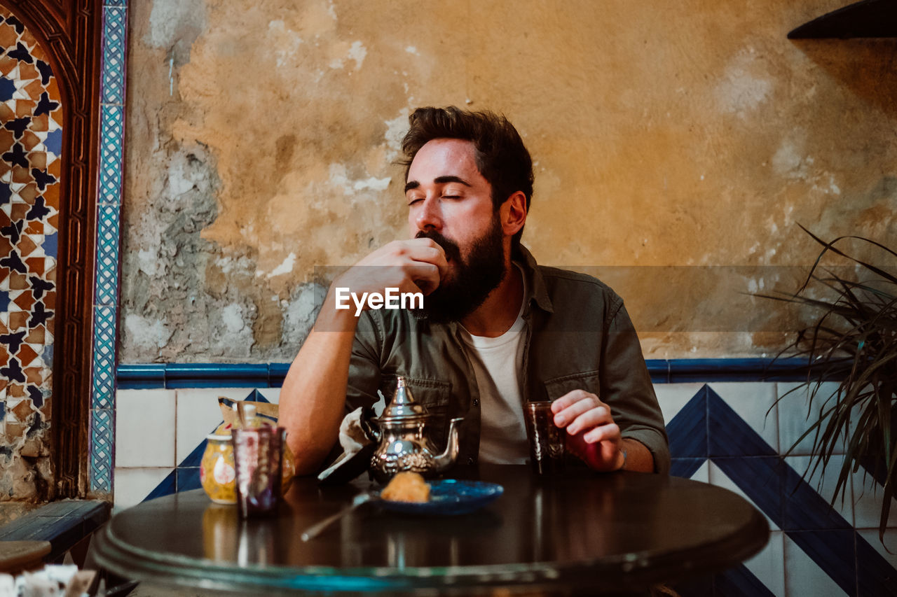Man eating food while sitting on table in restaurant