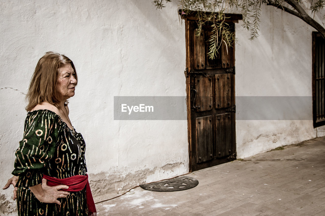 one person, built structure, real people, wall - building feature, architecture, women, standing, building, building exterior, side view, entrance, adult, door, clothing, lifestyles, young adult, leisure activity, young women, hair, fashion, beautiful woman, hairstyle, outdoors, contemplation