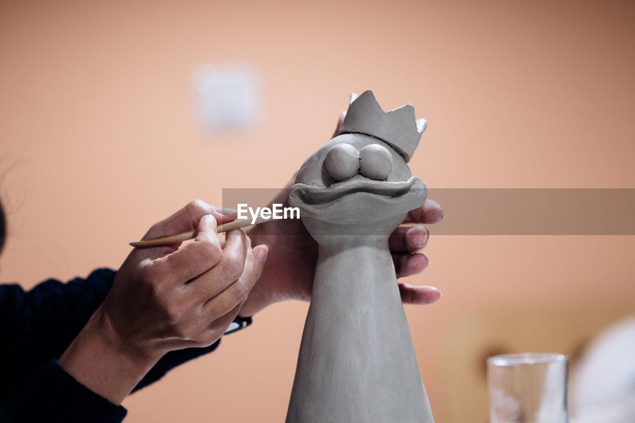 Cropped Image Of Artist Sculpting Bird At Workshop