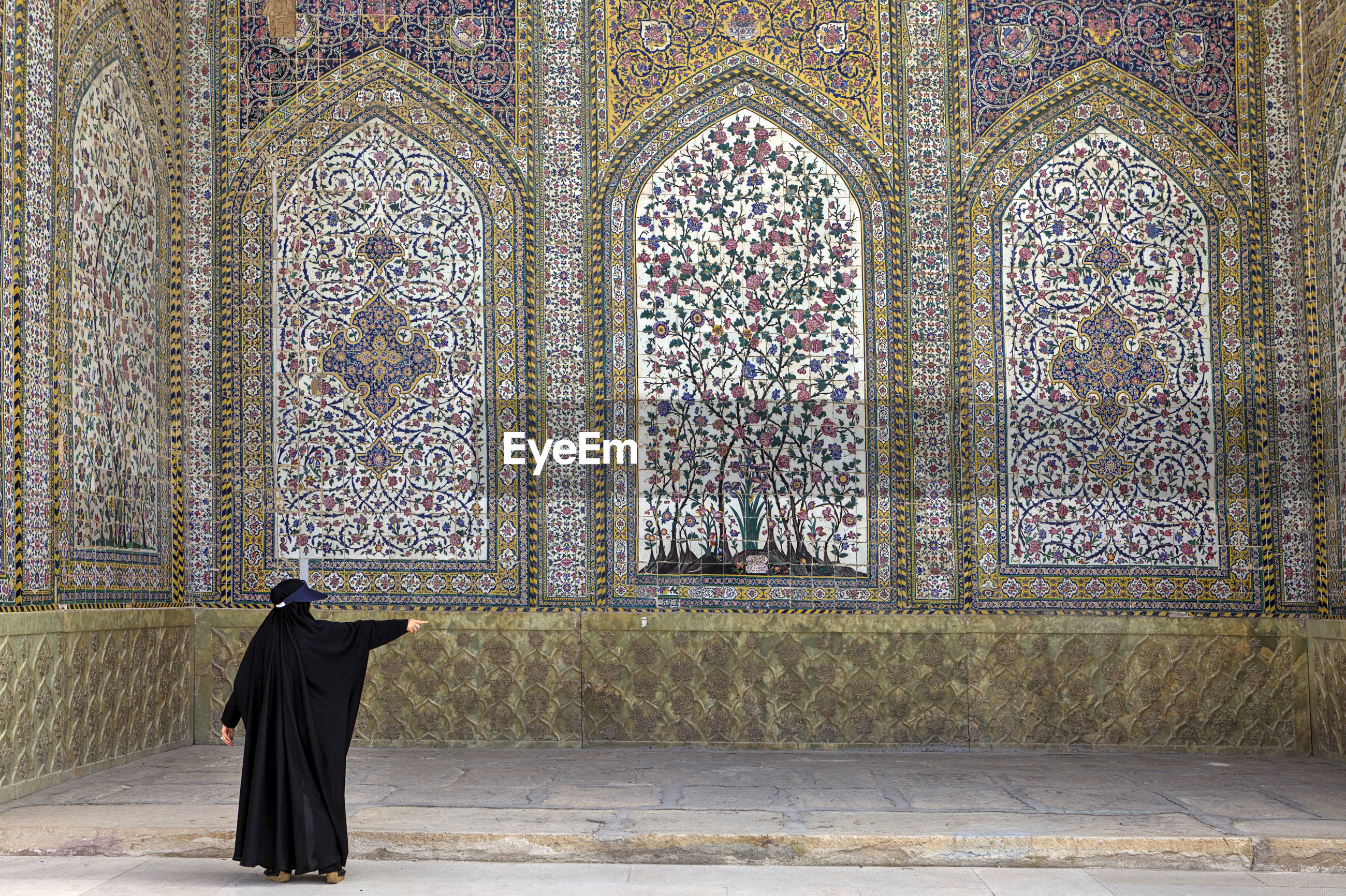 Rear view of woman standing against wall in mosque