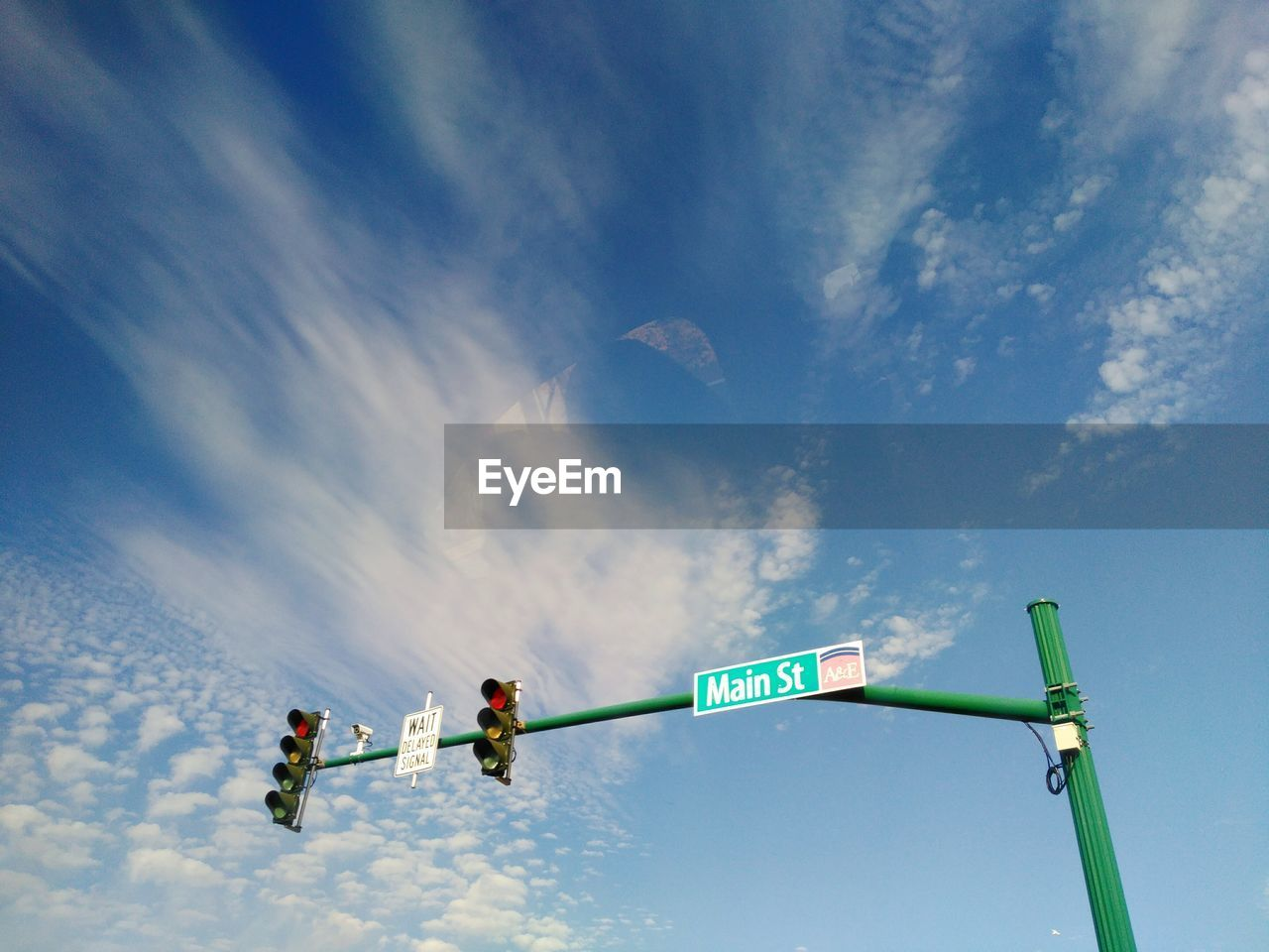 Low Angle View Of Sign Board On Traffic Light Pole Against Blue Sky