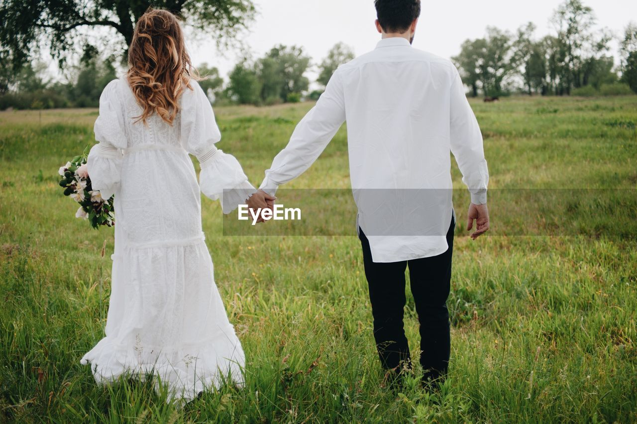 Rear View Of Wedding Couple Holding Hands While Standing On Grassland