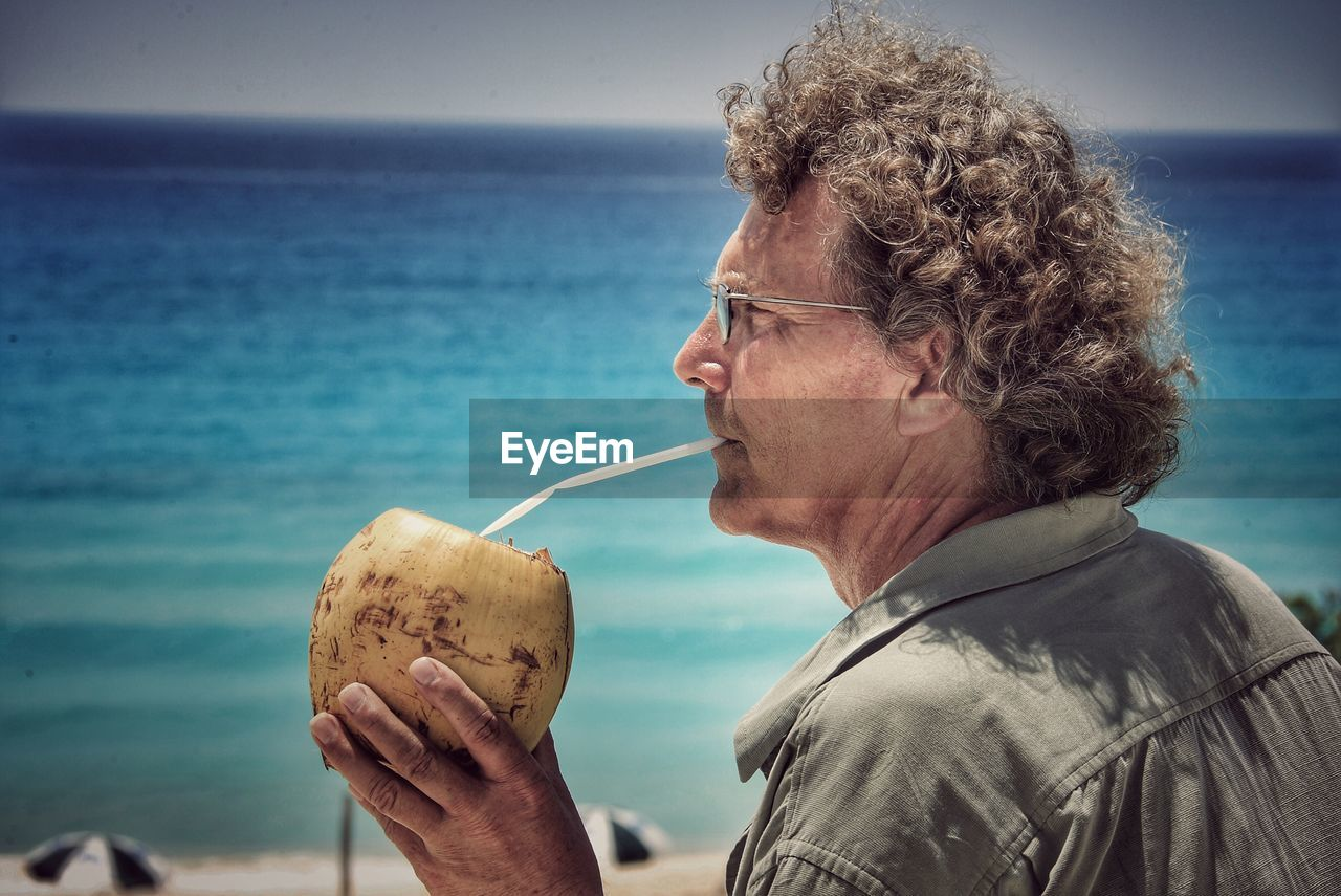 Mature man drinking coconut water against sea