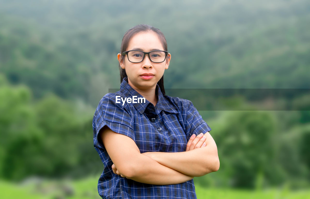 Portrait of young woman wearing eyeglasses while standing outdoors