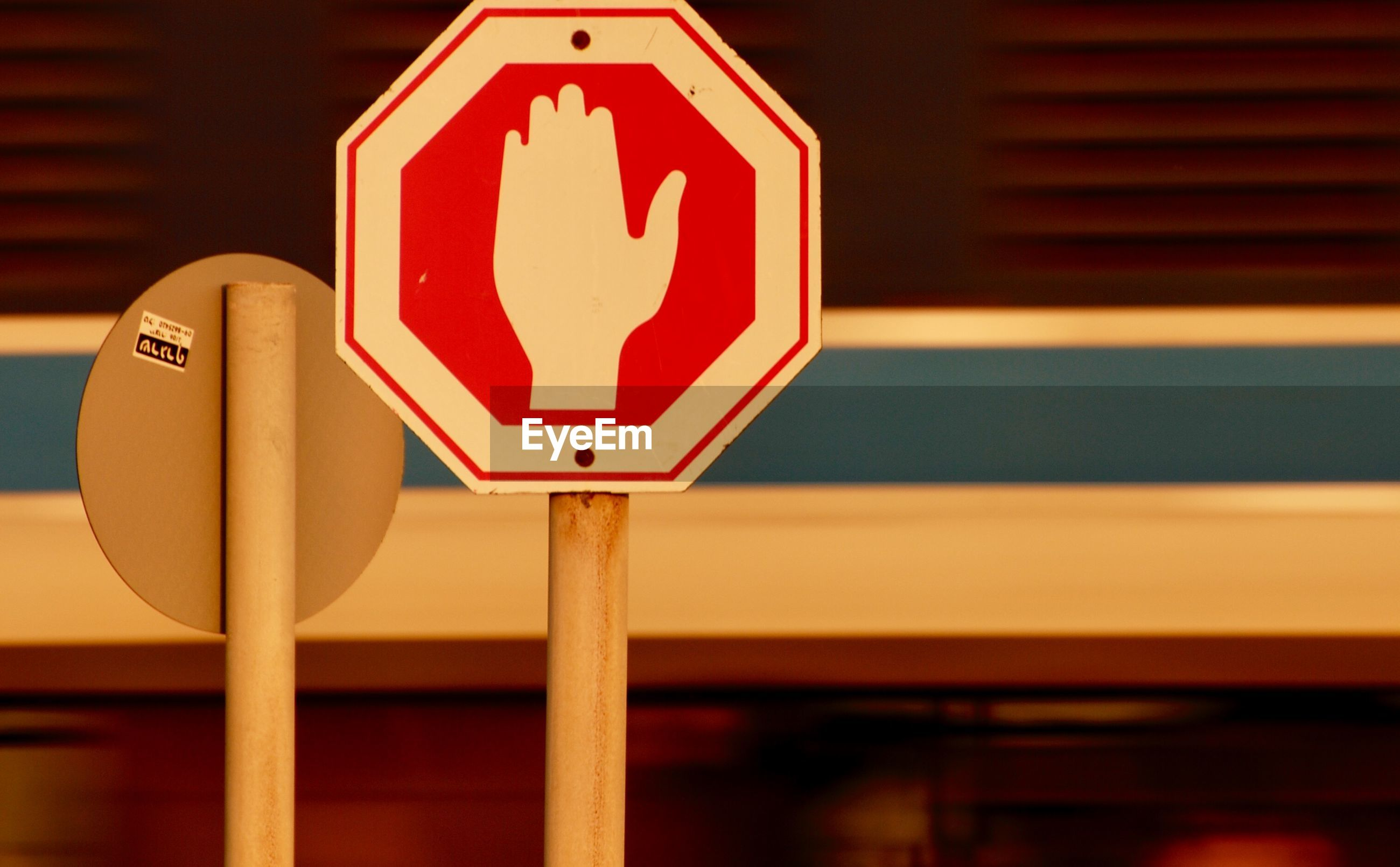 CLOSE-UP OF ARROW SIGN ON ROAD AGAINST BLURRED BACKGROUND