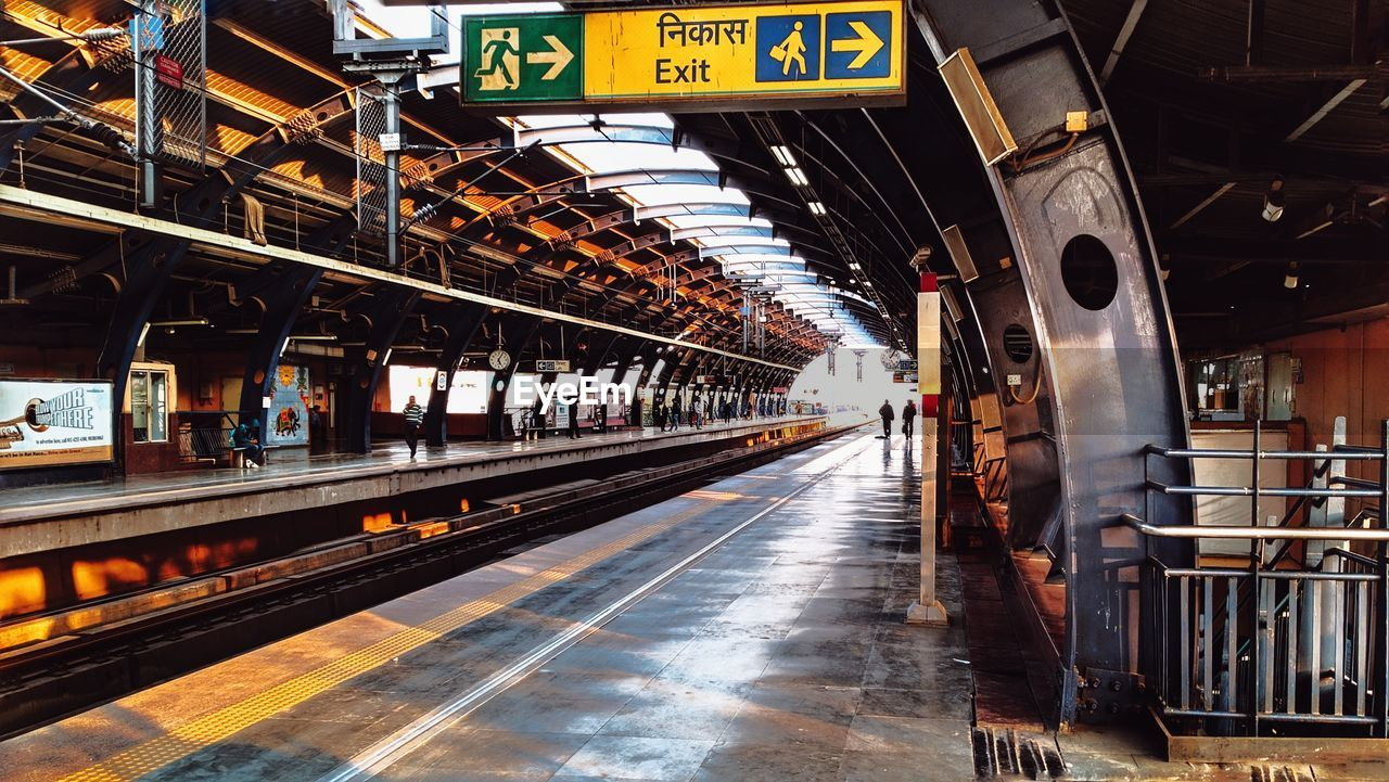 transportation, rail transportation, railroad station, railroad track, railroad station platform, public transportation, track, mode of transportation, architecture, travel, built structure, sign, indoors, train - vehicle, text, train, communication, day, incidental people, station