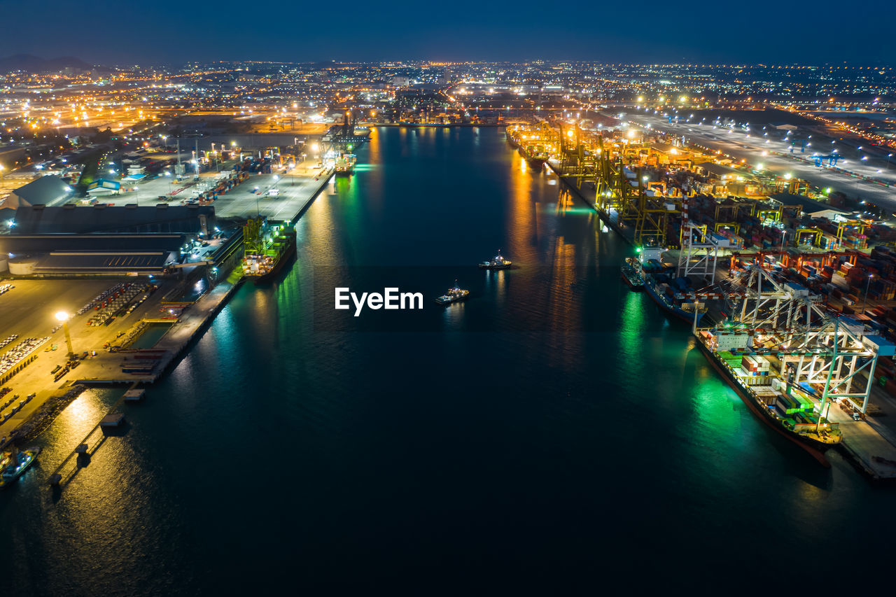 HIGH ANGLE VIEW OF ILLUMINATED CITY BY RIVER