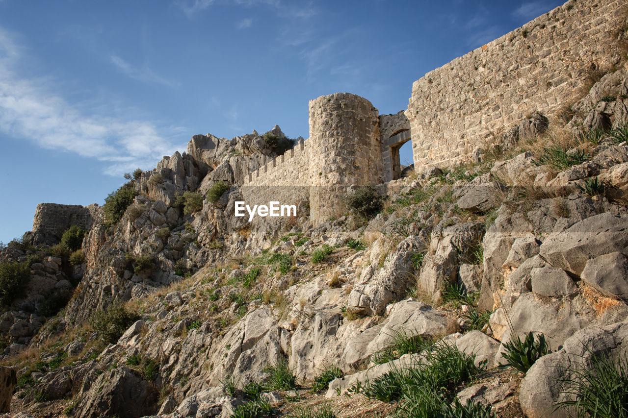 sky, built structure, architecture, rock, nature, history, mountain, rock - object, low angle view, rock formation, solid, the past, no people, day, building exterior, building, cloud - sky, land, ancient, scenics - nature, outdoors, ancient civilization, formation