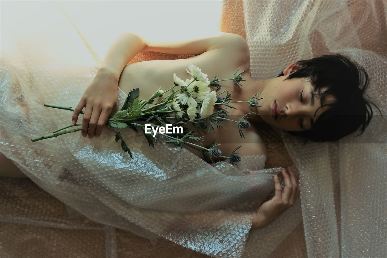High Angle View Of Naked Boy Holding Flowers While Lying With Bubble Wrap On Floor