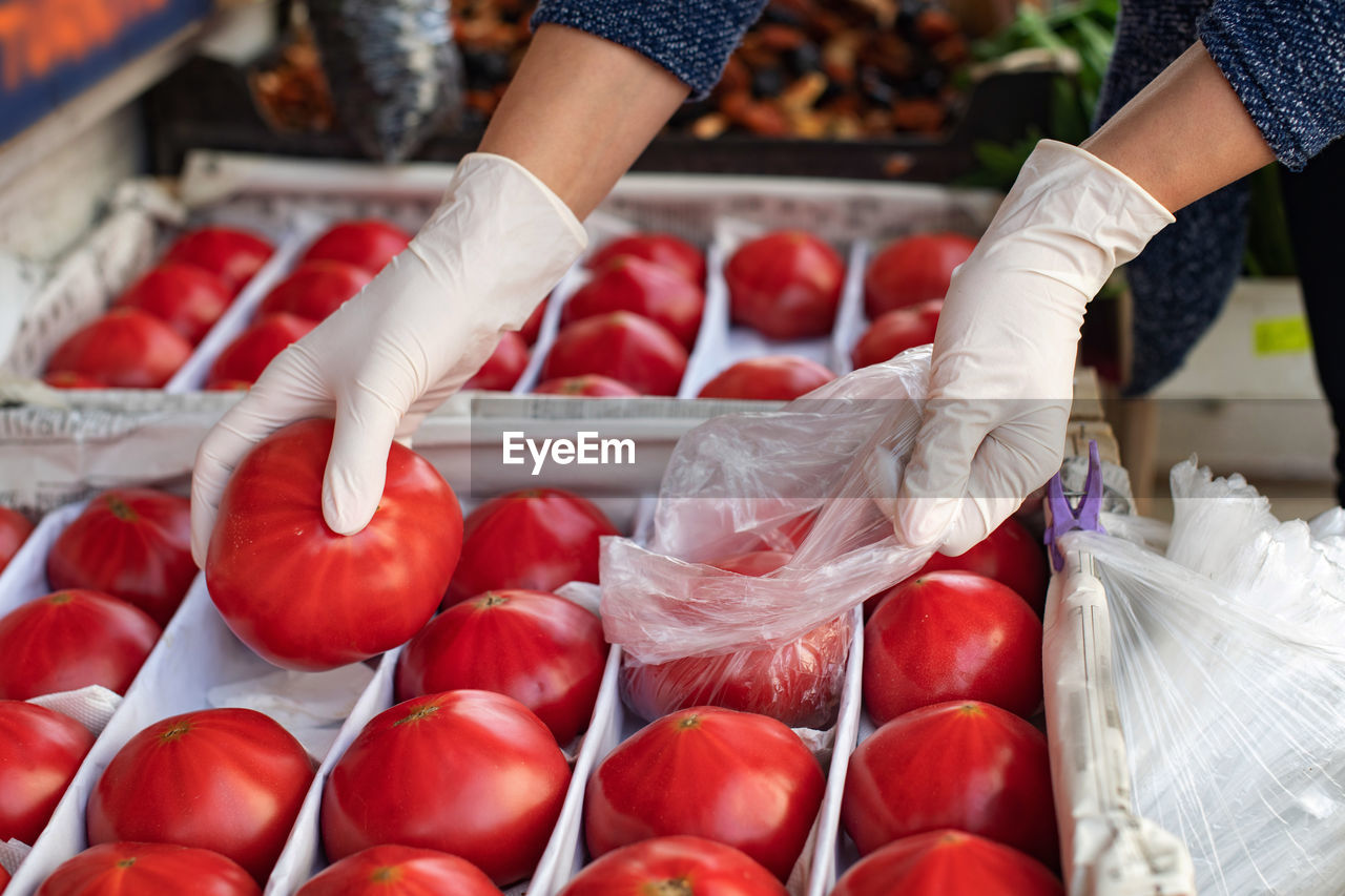 The concept of safe shopping. buying products  a woman in disposable gloves buys tomatoes