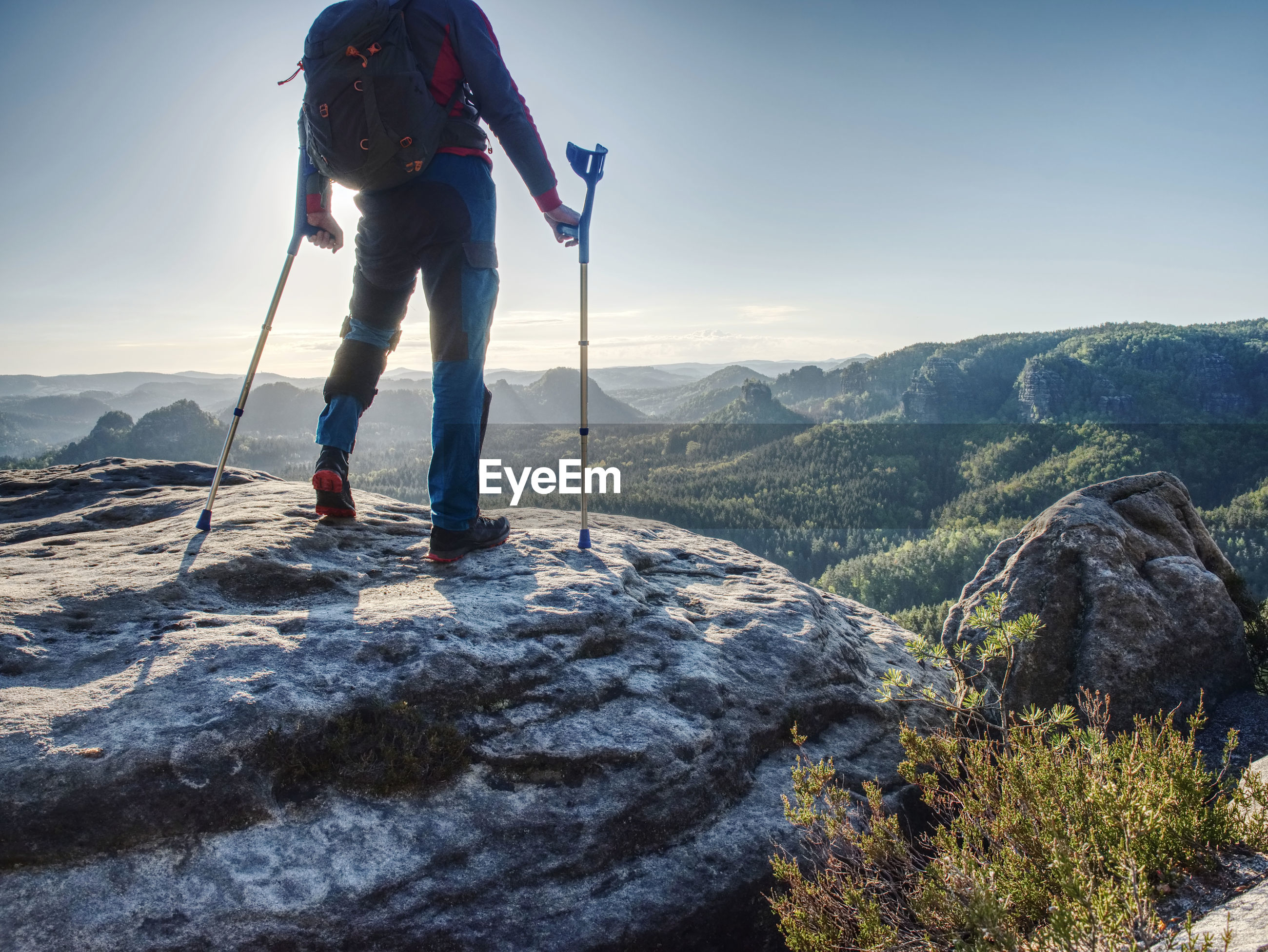 Hurt strong man stand with crutches on mountain.  elderly man walking with help of forearm crutchesg