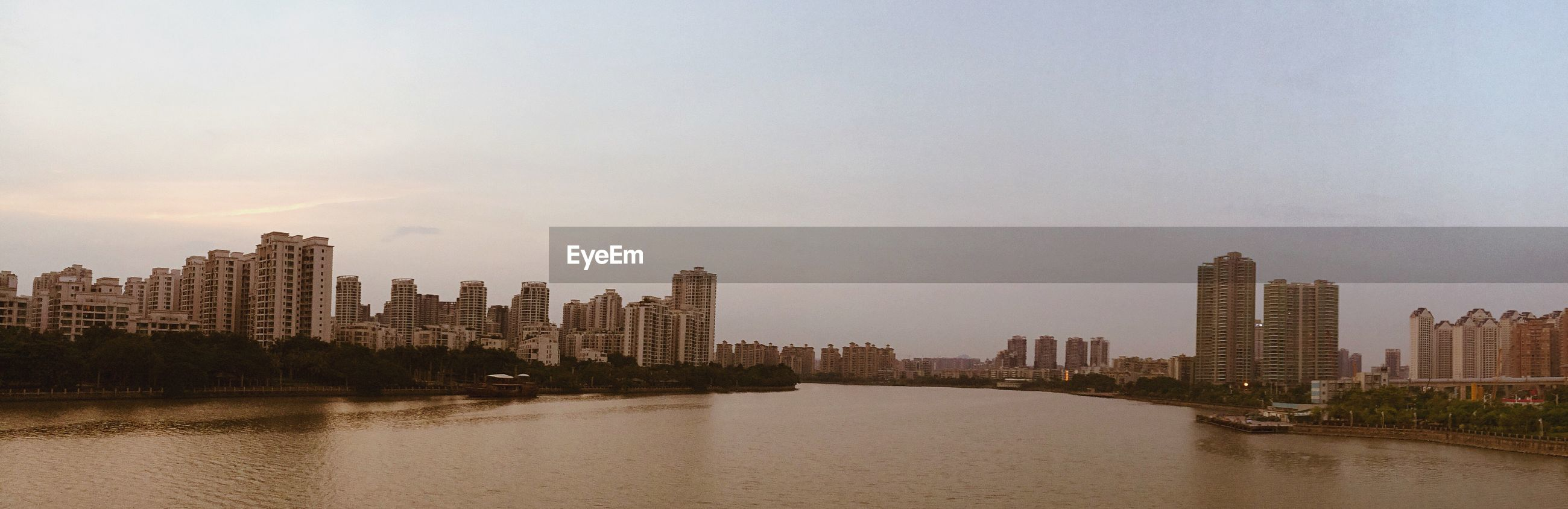 Panoramic view of river by city against sky during sunset