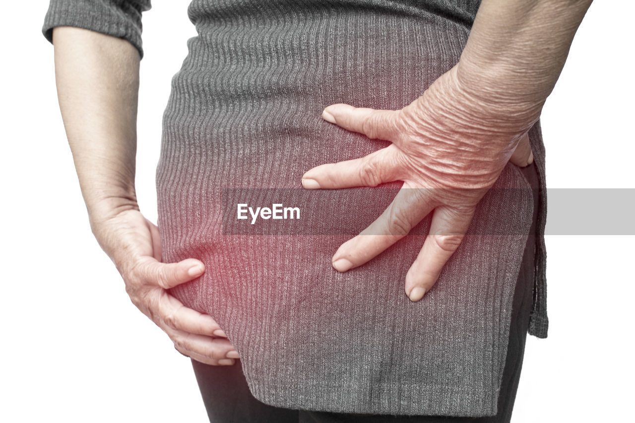 Midsection of woman massaging buttocks against white background
