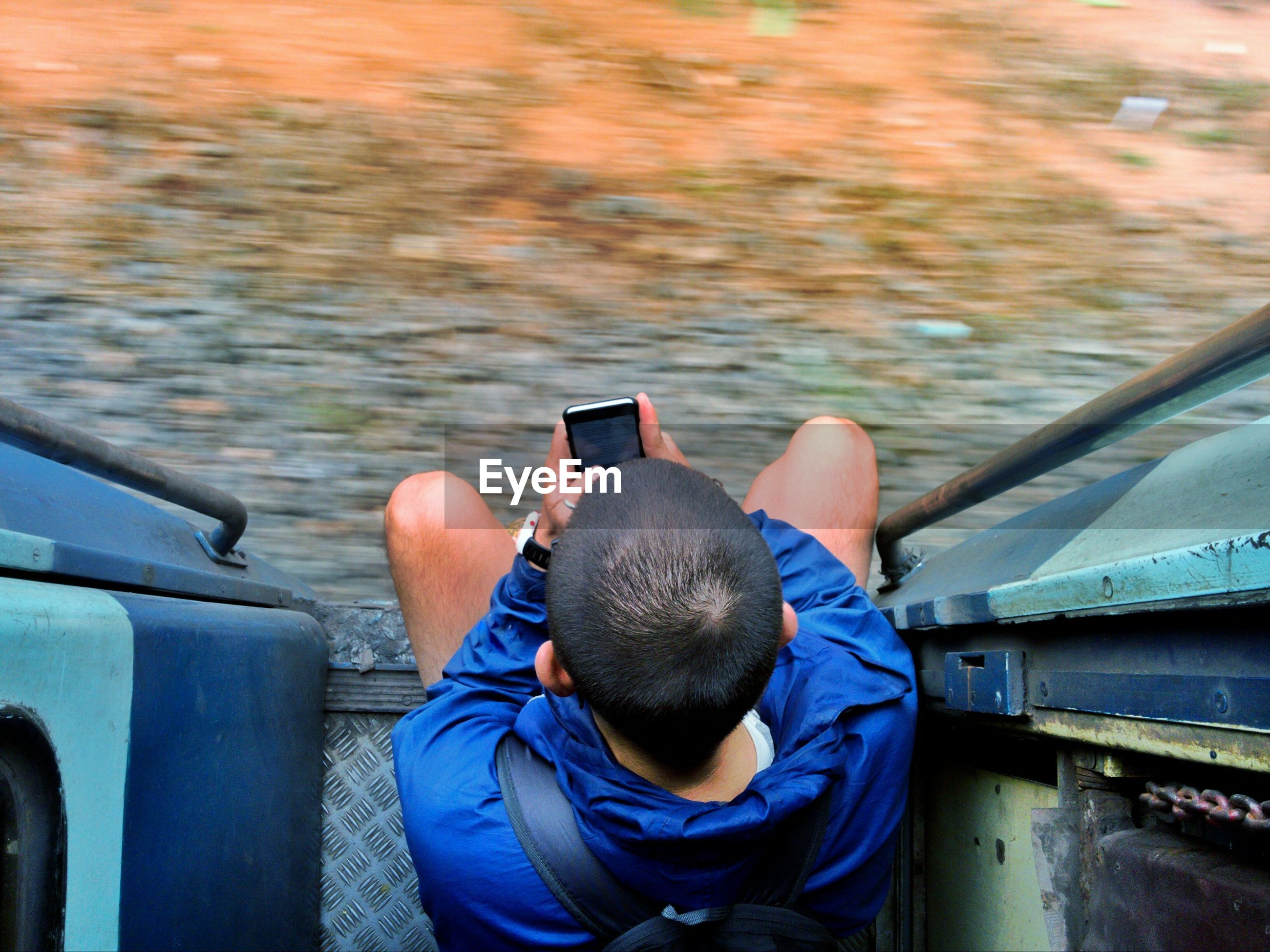 Directly above shot of boy using mobile phone at entrance of train