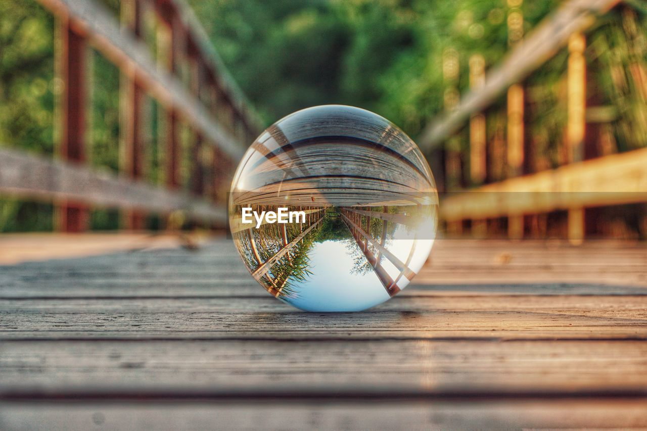 sphere, wood - material, no people, reflection, ball, day, glass - material, nature, close-up, table, railing, outdoors, focus on foreground, crystal ball, transparent, selective focus, single object, tree, still life, shape, glass